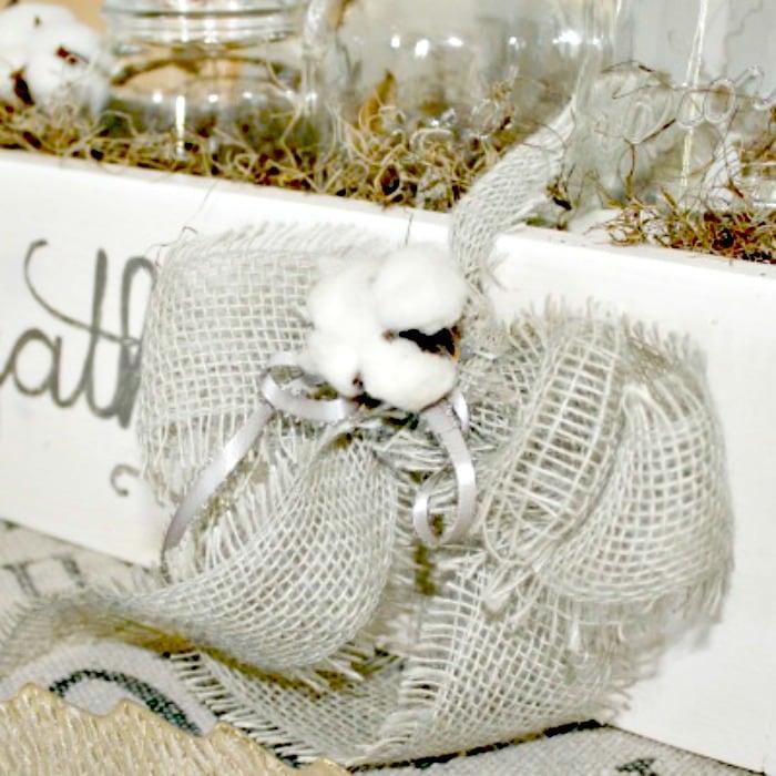 A pretty Farmhouse styled mason jar centerpiece in neutral fall colours. A cheap fall decor idea using a burlap ribbon and DIY cotton bole craft
