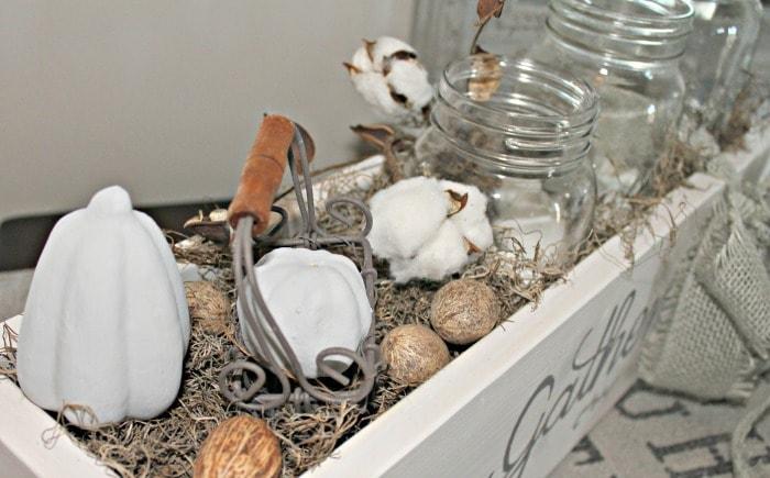 Mason jar centerpiece for fall decorating. It has cotton boles, nuts, pumpkins and raffia.