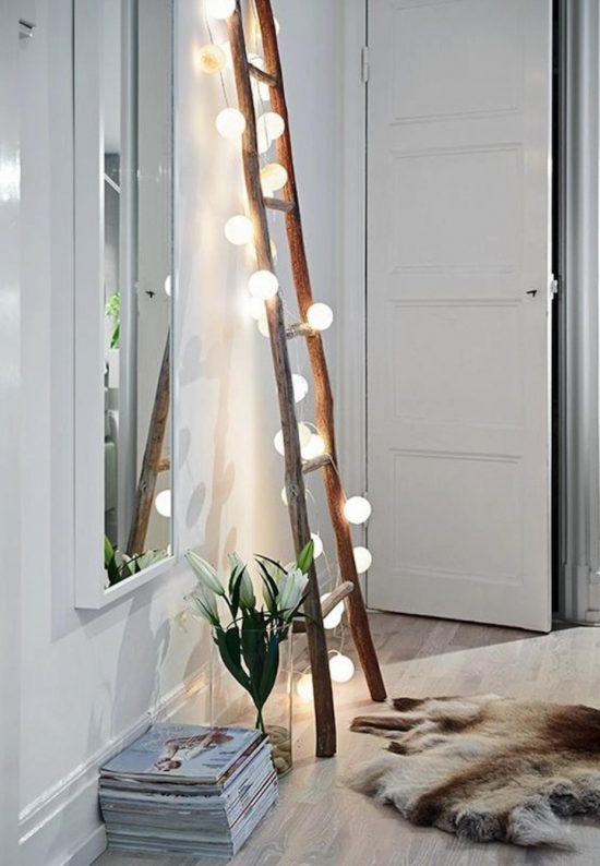 A string of globe lights cascading down a rustic ladder. A pretty fall home decor idea.