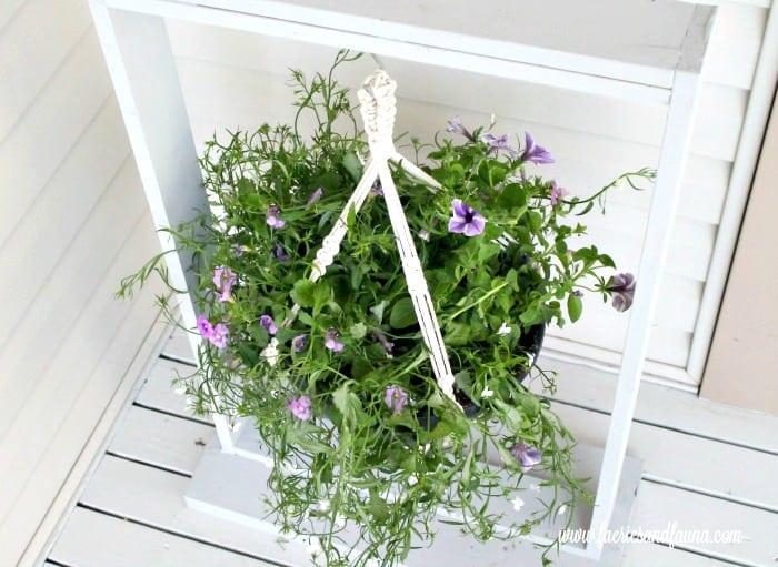 A DIY macrame plant hanger on a homemade wood pot holder frame.