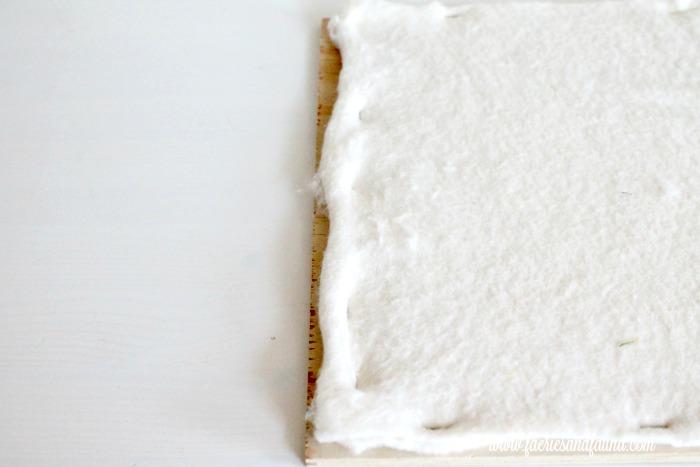 Adding quilt batting to a DIY bulletin board.