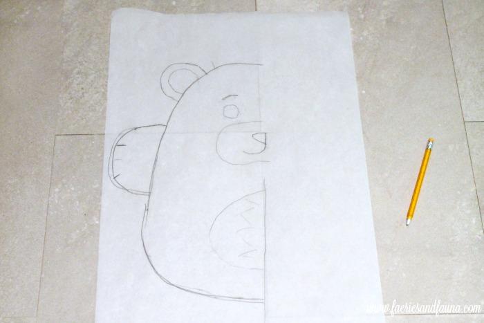 Transferring a Teddy bear DIY cushion pattern to parchment paper.