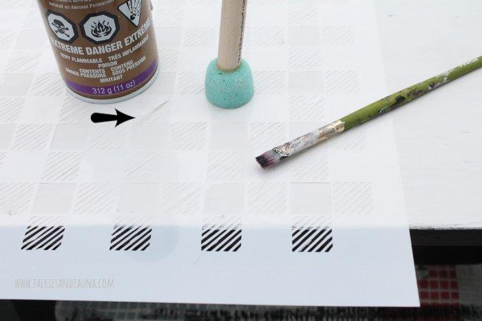 Applying a DIY buffalo check stencil to a vintage stool.