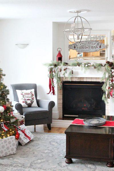 Adding ribbon to a Christmas fireplace mantel.