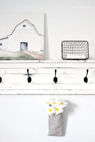 A handmade fabric pouch craft hanging on a shelf for farmhouse decor.